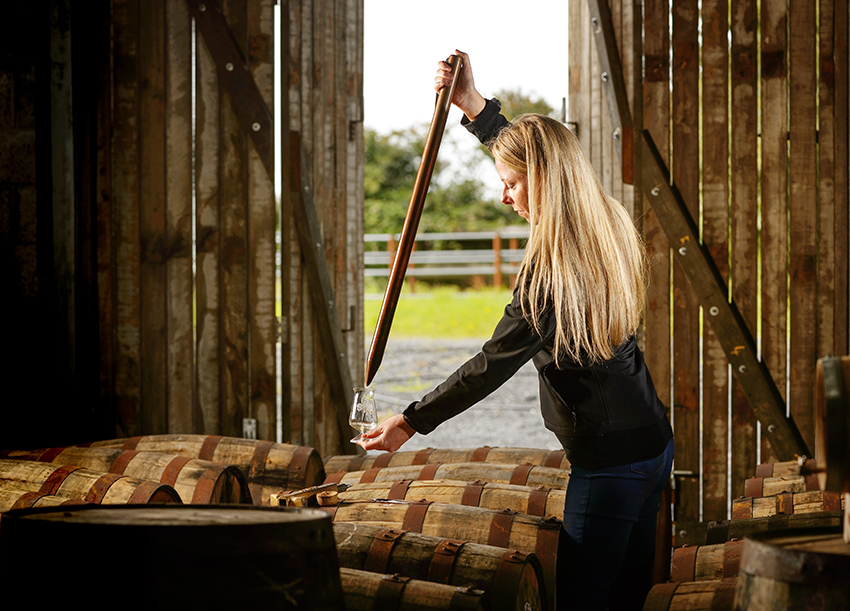 Louise McGuane taking a sample from a cask.